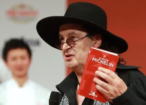 French chef Marc Veyrat holds a Michelin guide after being awarded the maximum three Michelin stars on 5 February 2018.