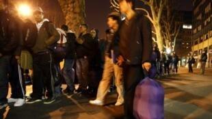 Des réfugiés afghans attendent un bus devant les amener dans un foyer pour y passer la nuit, le 01 avril 2009 à Paris.