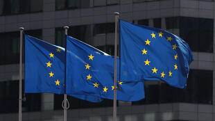 European Union flags fly at the EU's headquarters in Brussels. On Monday, the EU Commission proposed a 30 day travel ban on non-EU citizens to contain the coronavirus.