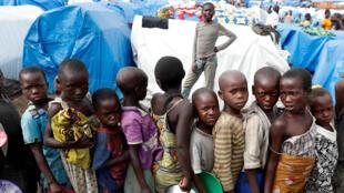 Des enfants attendent la distribution de nourriture dans un camp de personnes déplacées à Bunia, dans la province d'Ituri, est de la République démocratique du Congo, le 12 avril 2018.