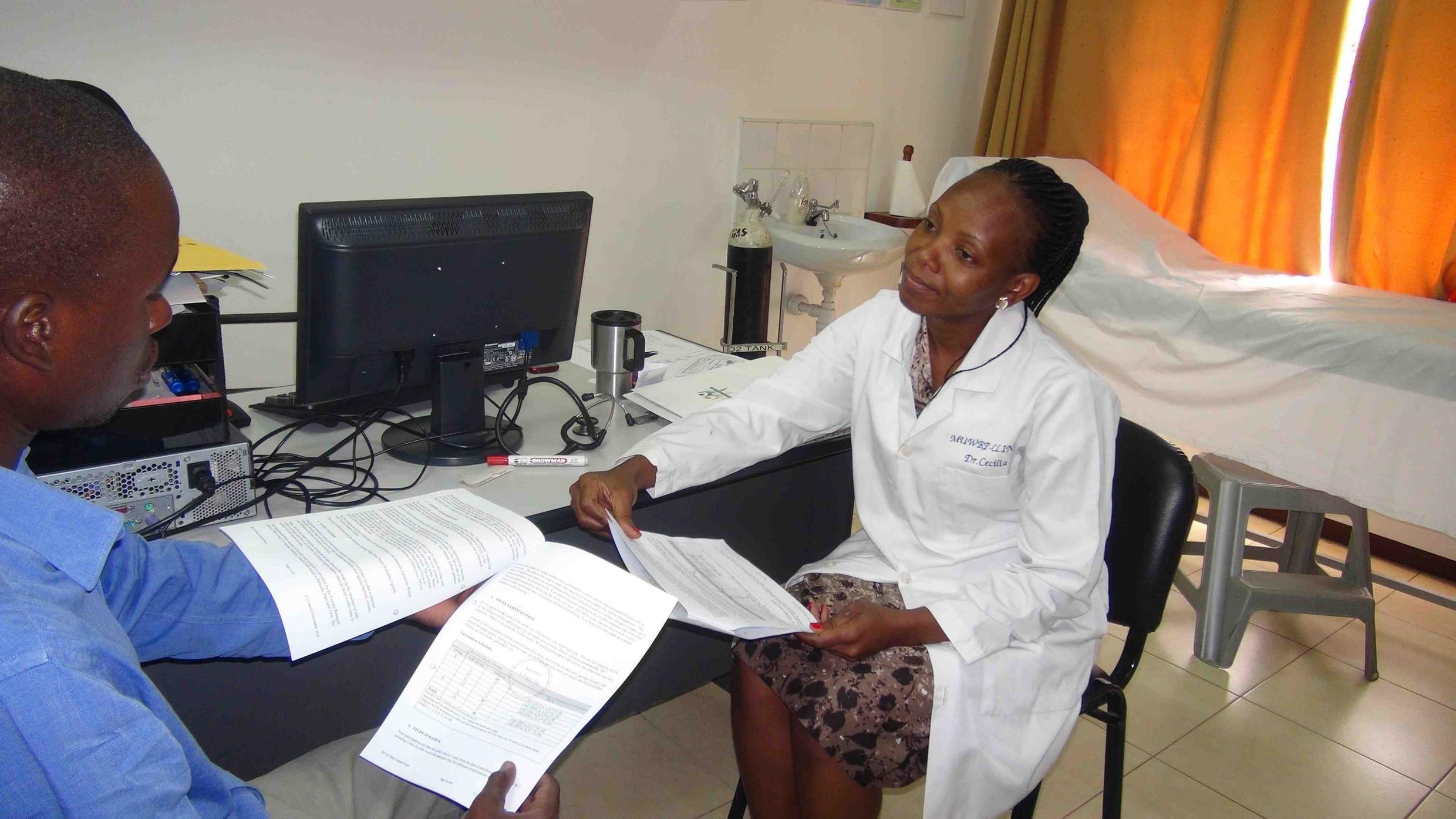 A research physician at Makerere University Walter Reed Project in Uganda discusses the Ebola vaccine study with a potential volunteer.