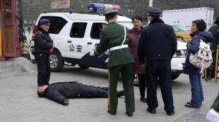 北京兩會期間,一名請願的訪民被警察攔下躺在人大會堂外的地上2013年3月6日北京
