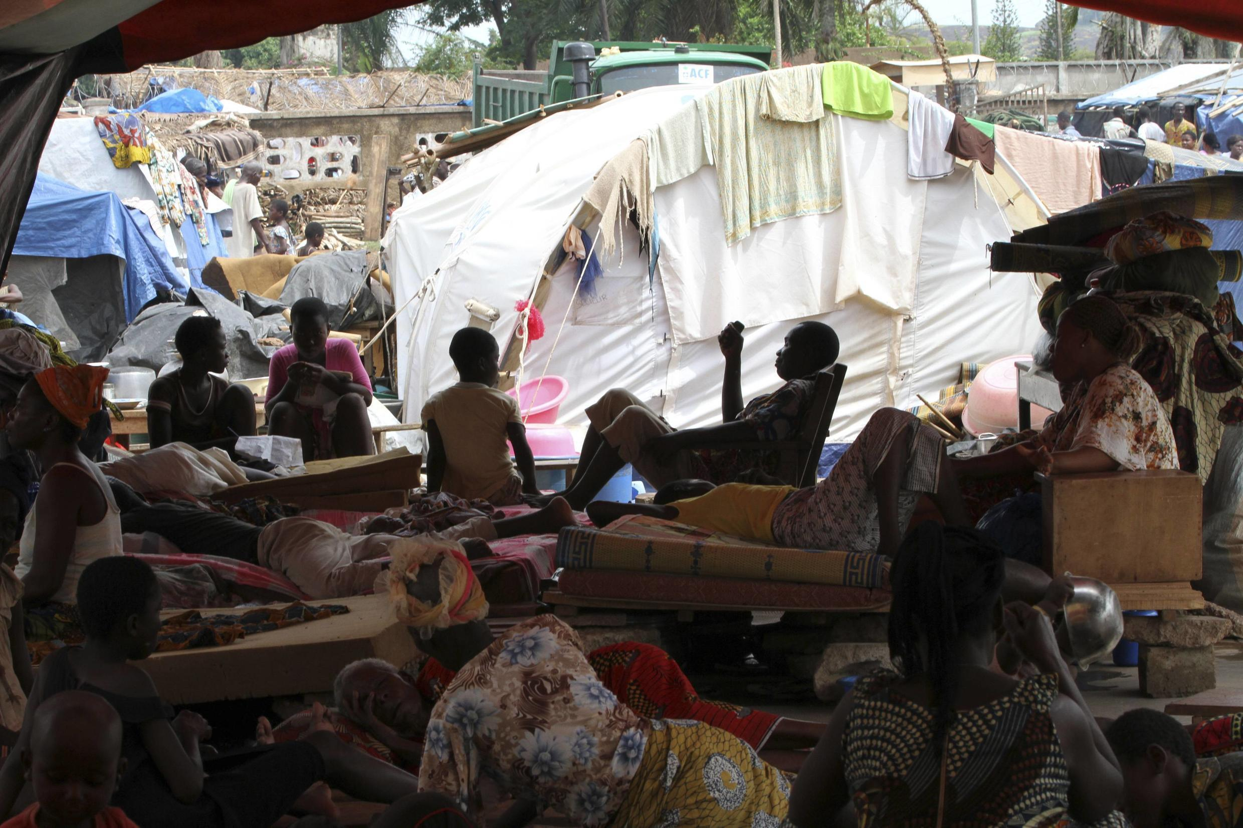 Refugees of the Guere ethnic group sit with their belongings inside a temporary camp set up at a Catholic church in Duekoue May 18, 2011.