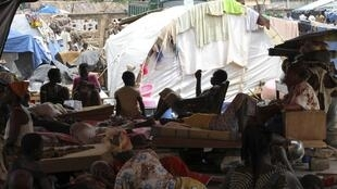 Refugees of the Guere ethnic group sit with their belongings inside a temporary camp set up at a Catholic church in Duekoue, Côte d'Ivoire, May 18, 2011.