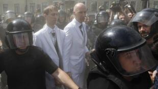 Casal homossexual é escoltado pela polícia para poder chegar a manifestação, atacada por militantes anti-gays.
