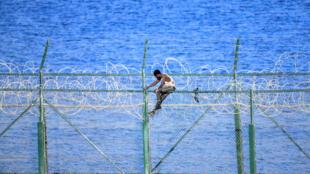 Un migrante trata de saltar la valla fronteriza entre Ceuta y Marruecos, el 30 de agosto de 2019 en la ciudad española en el norte de África
