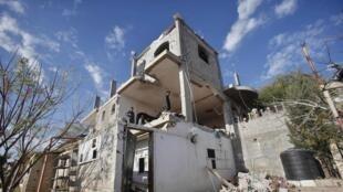 A Gaza, des Palestiniens inspectent les ruines d'une maison. Selon des témoins, elle a été détruite dans le raid israélien, le 25 décembre 2013.