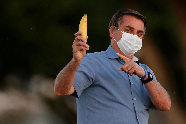 Le président brésilien Jair Bolsonaro brandit une banane avant une cérémonie à Brasilia, le 24 juillet 2020.