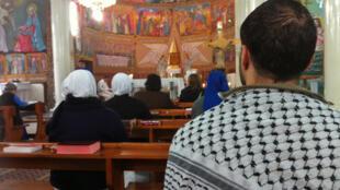 Des chrétiens célébrant la messe dominicale à l'église de la Sainte-Famille de Gaza.