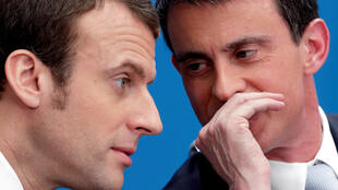 French Prime Minister Manuel Valls (R) speaks with then Economy minister Emmanuel Macron at the Elysee Palace in Paris, April 8, 2015.