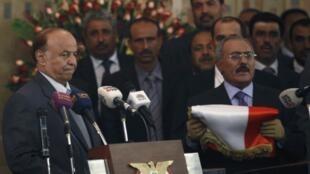 Sanaa, 27 février 2012. L' ex-président Ali Abdullah Saleh (1er rang, à g.) a remis le drapeau yéménite au nouveau chef de l'État yéménite (à dr.), élu le 21 février 2012.