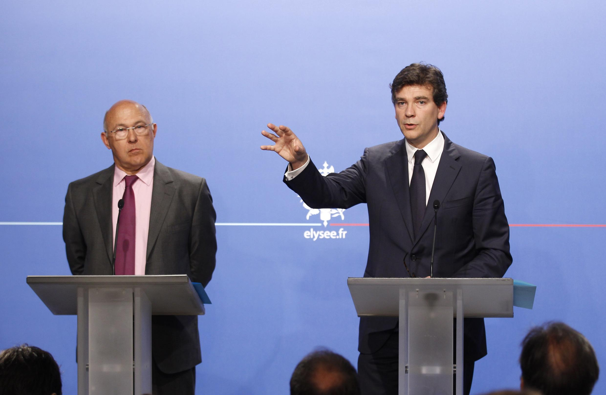 Industry Minister Arnaud Montebourg, near Michel Sapin (L), Employment and Social Dialogue Minister, announces the Car industry plan