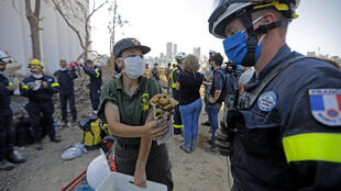 A Lebanese civil defence rescuer offers food to a member of the French rescue contingent.(Beirut, 7 August 2020)