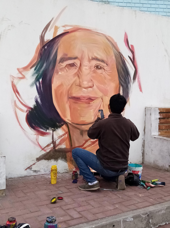 Daniel Manrique peint sur les murs de son quartier le portrait d'Eustacia, victime du Covid-19 à Lima.