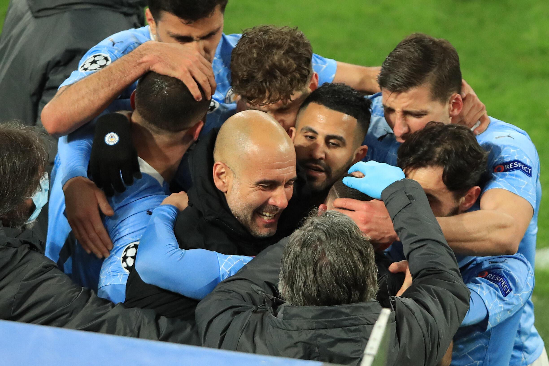 La joie de l'entraîneur espagnol de Manchester City, Pep Guardiola, et de ses joueurs, après un but marqué contre Dortmund, lors du quart de finale retour de la Ligue des Champions, le 14 avril 2021 à Dortmund