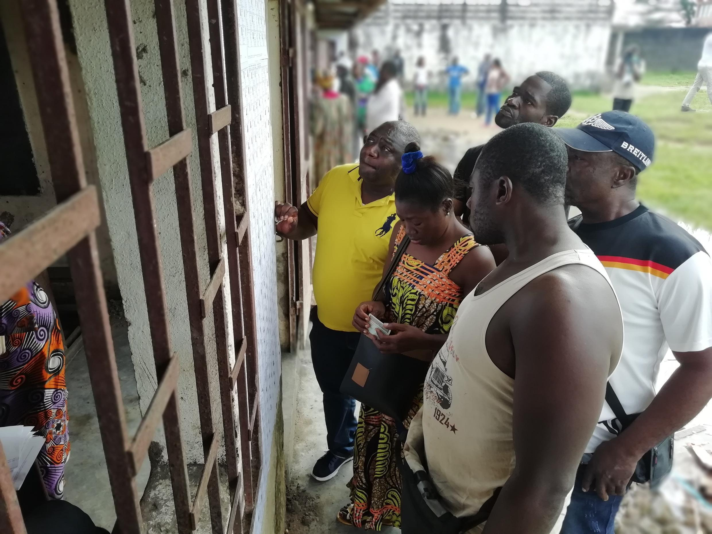 People search for their names on voter lists outside a polling station at the New Bell Youth Centre in Douala, 7 October 2018.