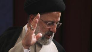 El ultraconservador Ebrahim Raisi saluda después de haber votado en Teherán, el 18 de junio de 2021
