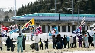 Des Japonais saluent le passage du nouveau Shinkansen reliant Tokyo à l'île d'Hokkaido, le 26 mars.