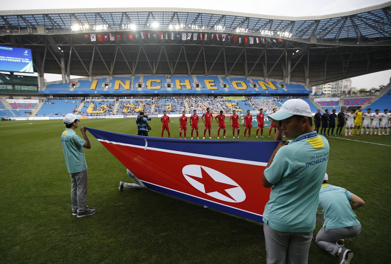 Des volontaires sud-coréens portent le drapeau nord-coréen à l'intérieur du stade de football  d'Incheon, le 17 septembre 2014, drapeau qui ne peut être déployé qu'à l'intérieur des stades, lors des Jeux asiatiques.