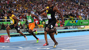 Le sprinteur ivoirien Ben Youssef Méité (en orange et vert) observe le Jamaïcain Usain Bolt, à l'arrivée de la finale du 100 mètres des JO 2016.