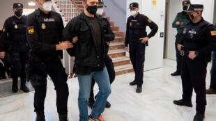 Policías escoltan al serbio Norbert Feher (centro), conocido como 'Igor el Ruso', a su llegada al juicio por triple homicidio en la Audiencia Territorial de Teruel, en España, el 12 de abril de 2021