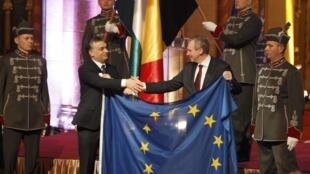 Le Premier ministre belge Yves Leterme (d) tend le drapeau européen à son homologue hongrois Viktor Orban lors de la cérémonie de passation de pouvoir à Budapest, le 6 janvier 2011.