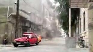 Une voiture de police en flammes lors d'une manifestation contre le régime à Homs.