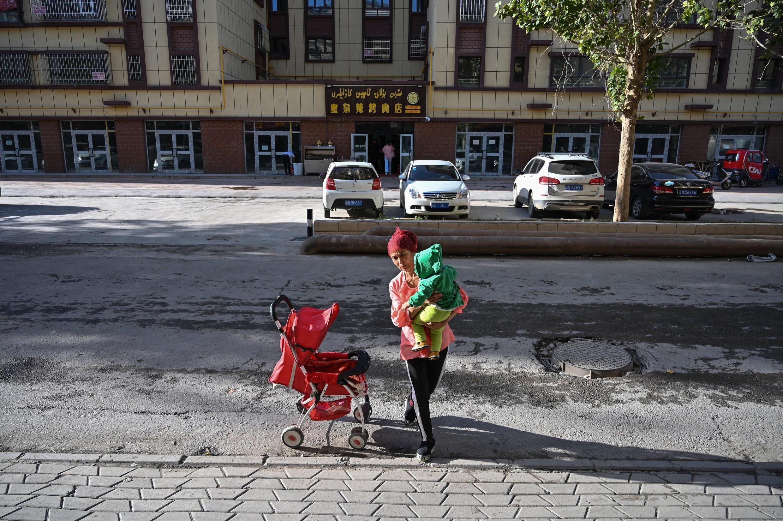 Una mujer pasea con un bebé por el barrio uigur de la ciudad china de Aksu, en la región de Xinjiang, el 11 de septiembre de 2019