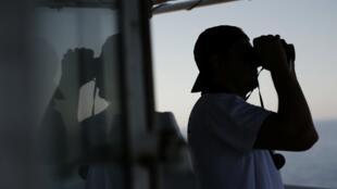A bordo del Acuarius, un miembro de la ONG SOS Mediterráneo usa binoculares para mirar el mar luego de recibir el llamado de urgencia de una embarcación en peligro. 23 de Junio de 2018, mar abierto de Túnez.