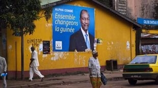 Pedestrians walk past a poster for Guinea presidential candidate Alpha Condé in Conakry, 13 September 2010.