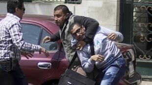 Un policier égyptien en civil a arrêté un étudiant partisan des Frères musulmans devant la faculté de médecine au Caire, lors d'une manifestation contre les militaires et le gouvernement le 9 avril 2014.