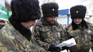 Policías rusos examinando retratos de sospechosos de los atentados de Volgogrado.