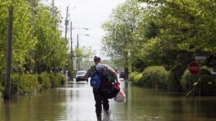 Un homme marche dans les rues pleines d'eau de Saint Blaise au Québec.