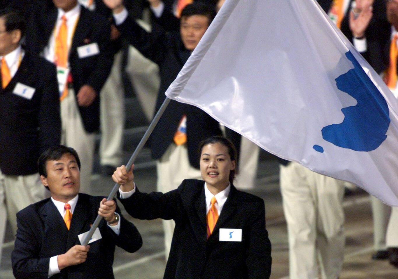 VĐV Bắc Triều Tiên Jang Choo Pak (T) và Eun-Soon Chung của Hàn Quốc cùng giương lá cờ biểu tượng thống nhất tại lễ khai mạc Olympic Sydney, 15/09/2000.