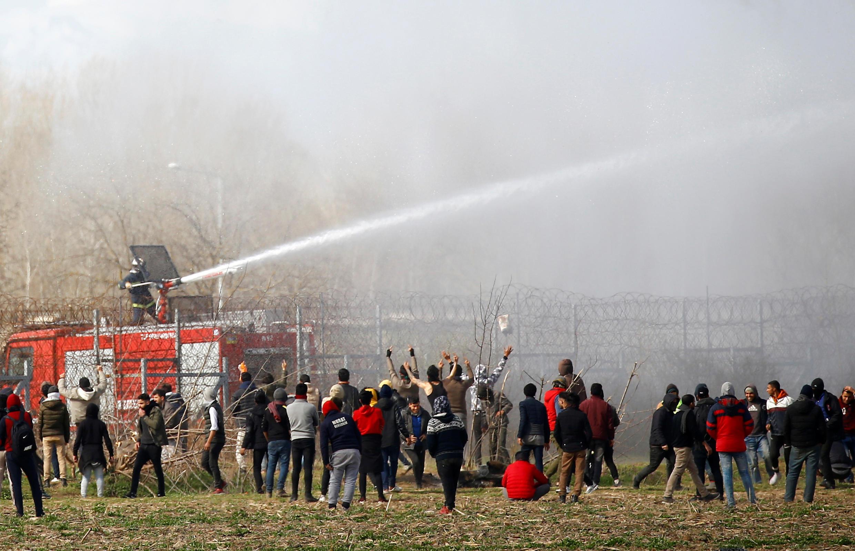 Les Grecs utilisent des canon à eau face aux migrants rassemblés à la frontière turco-grecque près du poste-frontalier de Pazarkule en Turquie, le 7 mars 2020.