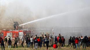 Les Grecs utilisent des canon à eau face aux migrants rassemblés à la frontière turco-grecque près du poste frontalier de Pazarkule en Turquie avec la Grèce Kastanies, à Edirne, en Turquie, le 7 mars 2020.