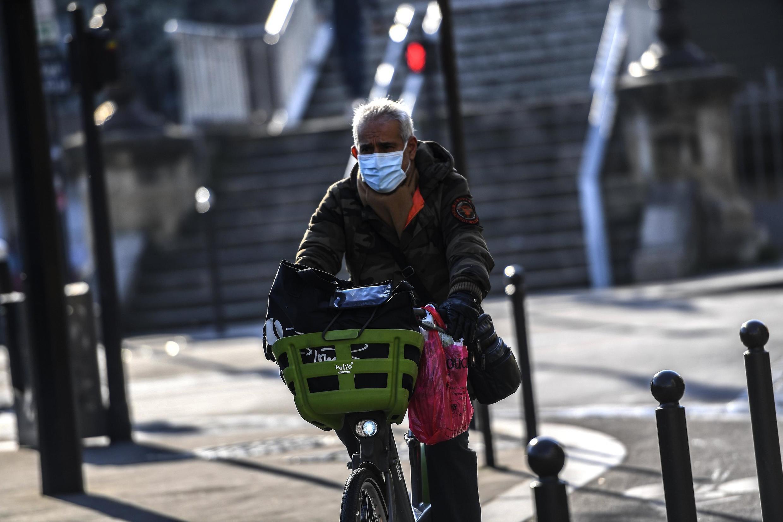 Un hombre con mascarilla pedalea por las calles de París.