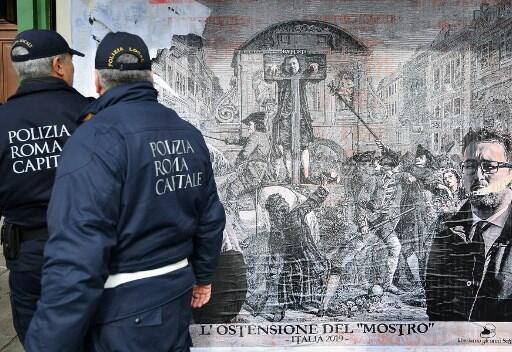 Um coletivo artístico protestou com uma obra polêmica diante da sede do Ministério da Justiça. O quadro mostrava o ministro do Interior, Matteo Salvini, e o ministro da Justiça como dois algozes triunfantes diante de um pelourinho no qual estava pendurado.