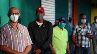 Des habitants de la République Dominicaines portent le masque en faisant la queue lors des élections générales le 5 juillet 2020.