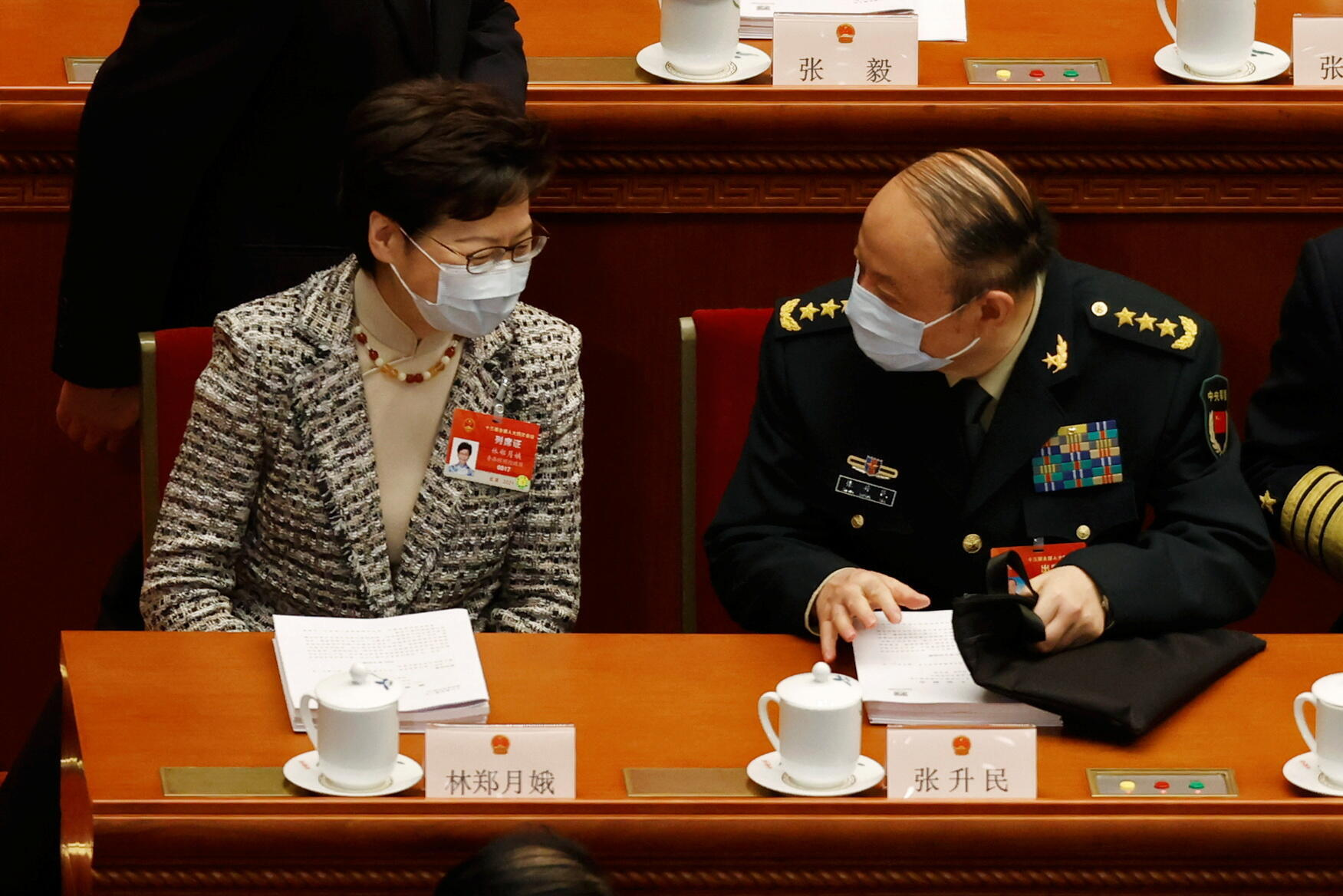 Hong Kong Chief Executive Carrie Lam chats with a military delegate before the opening session of the National People's Congress (NPC) at the Great Hall of the People in Beijing, China March 5, 2021