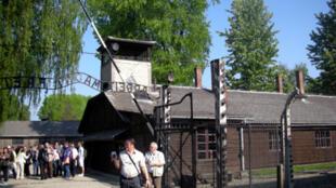 """L'entrée du camp d'Auschwitz avec, au second plan, le panneau volé avec l'inscription tristement célèbre """"Arbeit macht frei"""" ."""
