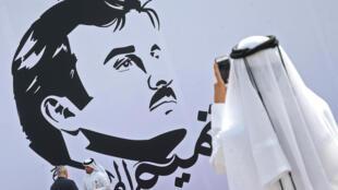 Un qatarien photographie un portrait de l'émir Tamim intitulé «Tamim le glorieux», le 13 juillet lors d'une exposition à Doha.
