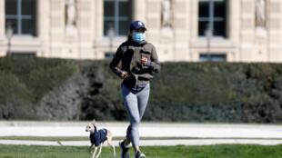 Una mujer corriendo con una mascarilla en los Jardines de las Tullerías de París, el 23 de marzo de 2020.