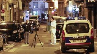 Un policier et un membre de la police scientifique étudient les alentours de l'attaque au couteau dans le centre de Paris, le 12 mai 2018.