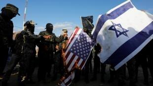 Des combattants du groupe palestinien Jihad Islamic brûlent des drapeaux américains et israéliens, lors d'une manifestation anti-israélienne, au sud de la Bande de Gaza, le 10 octobre 2020.
