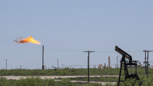 A flare stack is pictured next to pump jacks and other oil and gas infrastructure on April 24, 2020 near Odessa, Texas