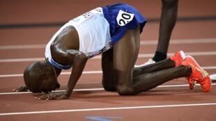 El atleta británico Mo Farah besa el suelo tras cruzar primero la línea de meta en los 10.000 metros.