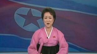 Uma apresentadora da televisão norte-coreana anuncia o sucesso do lançamento do foguete.