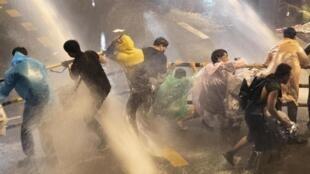 Des militants pro-démocratie font face aux canons à eau, le 16 octobre à Bangkok.
