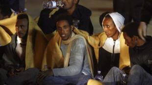 Des immigrants clandestins sécourus par les gardes côtes italiens, assis au port de Pozallo en sicile du sud, le 26 octobre 2009.